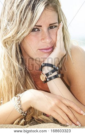 Young beautiful blonde hair model girl at the seaside with freckles. Summer. A beautiful and stunning blonde girl is lying on the beach and resting his elbows on the ground. She has one hand on his face. Wearing accessories, bracelets.