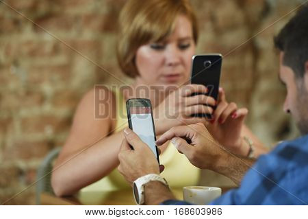 young American couple at coffee shop with man and woman close up hands using their mobile phone networking ignoring each other in relationship communication problem and internet addiction