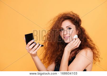Close up portrait of a smiling pretty woman with red hair doing make up and looking at camera isolated on orange