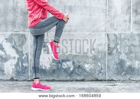 Fitness sport woman in fashion sportswear doing yoga fitness exercise in the city street over gray concrete background. Outdoor sports clothing and shoes, urban style.
