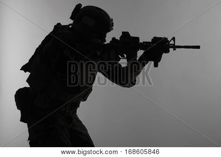 United states Marine Corps special operations command Marsoc raider with weapon aiming a gun. Silhouette of Marine Special Operator gray background
