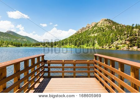 Wooden berth on lake against Rocky Mountain