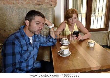 young American couple at coffee shop with internet and mobile phone addict woman ignoring bored sad and frustrated man boyfriend or husband in relationship problem and addiction concept