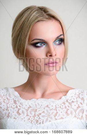 Studio fashion shot: a beautiful young woman in white dress
