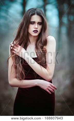 Outdoor portrait of a lovely sad young woman
