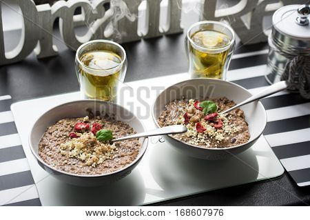 Chocolatiers breakfast for two person with oatmeal, puffed rice, cereals , dried strawberries and  tea prepared in a white bowl. Big inscription Dream above.