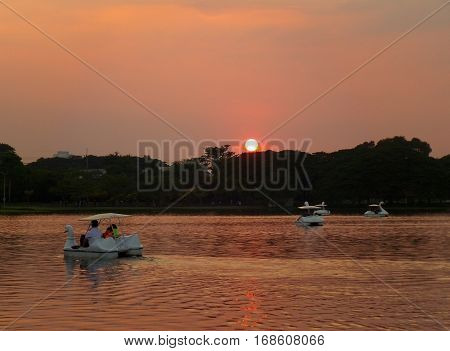 People enjoying pedal boat ride on the lake at sunset, public garden in Bangkok, Thailand