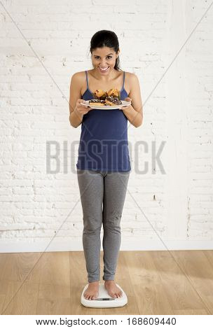 young attractive slim latin woman or teenager girl checking weight on scale holding muffin and chocolate donut smiling happy and satisfied in weight loss success and diet concept