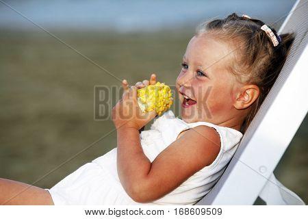 Little Funny Girl Eating A Boiled Corn