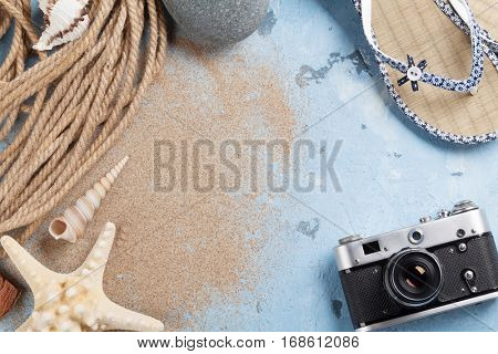 Beach vacation background. Camera, starfish and flip-flops on stone backdrop with sand. Top view with copy space.