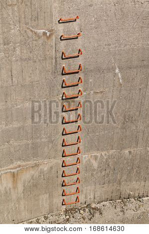 Metal steps of a ladder in a concrete wall beloning to a reservoir lake dam.