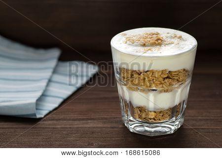 Yogurt parfait with granola on wooden background