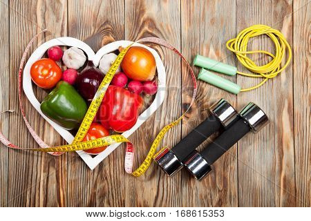 Sport and diet. Vegetables dumbbells and centimeter. Peppers tomatoes garlic onions and radishes in the heart on rustic background