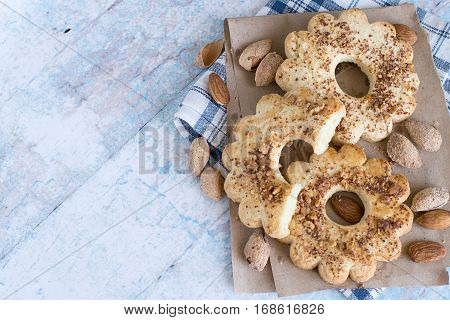 Almonds and ring cookies, strewed with chopped nuts, on paper and on a checkered napkin on an old wooden table.