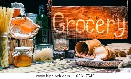 Warm-lighted counter of grocery store. Flour, cereal, pasta, sugar, honey and other grocery goods. Vintage style. Natural wood, paper and glass materials
