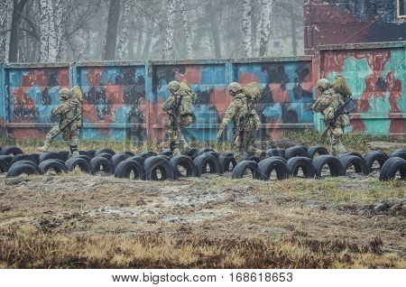 Ukrainian soldiers run with duffel bags during military training