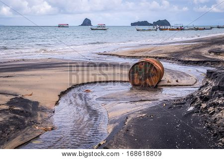 Rusty barrel oil on a partly black coloured beach illustrates the pollution of environment by oil spills. Longtail boats in the background.