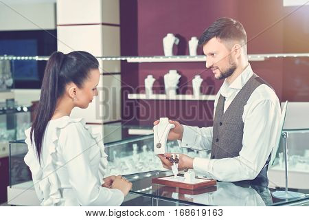 Jeweler young brunet man with beard showing for female buyer necklace of gold jewelry set with black stones. Side view of woman in blue blouse choosing present and want buying jewelry for herself.