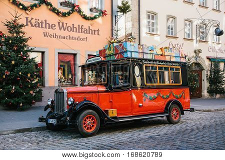 Rothenburg ob der Tauber, Germany, December 30, 2016: Decorated in retro style Christmas red car next to a toy store in Rottenburg ob der Tauber in Germany in Europe