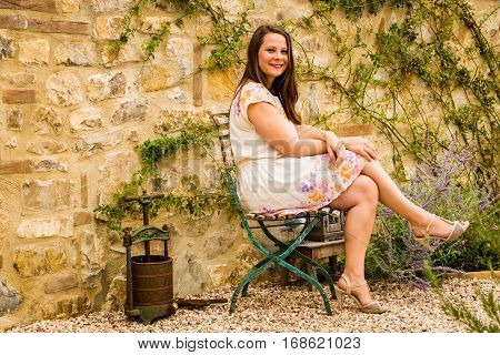 Girl Sitting On The Chair In Beautiful Dress Enjoying Summer