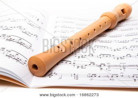 Wooden flute on sheet music. Close up.