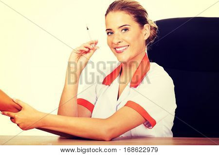 Young female doctor or nurse giving an injection
