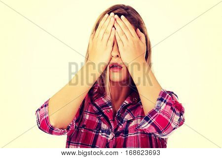 Woman covering her eyes with hands. See no evil concept