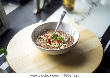 Chocolatiers breakfast   with oatmeal, puffed rice, cereals , dried strawberries and  tea prepared in a white bowl.