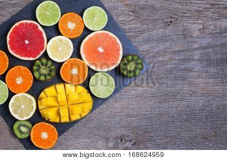 Raw fruit rich in vitamin C on the black slate platter: oranges grapefruits lemons limes kiwis slices, top view, copy space