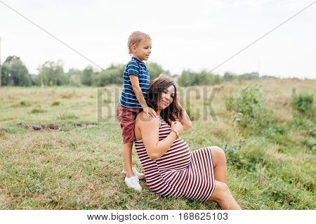 Pregnant Woman Sitting Countryside With Her Son.