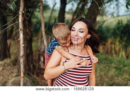 Pregnant Woman Hugging With Her Son.