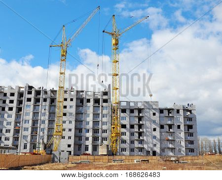 Two Building Cranes and Building High Rise with Copy Space. Building Development with Cranes Construction.