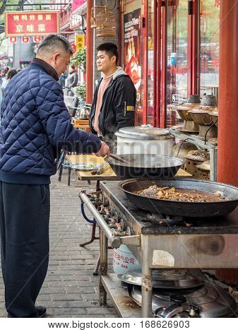 Beijing, China - Oct 30, 2016: Street food; man cooking hot food for outdoor sale using a modern gas-powered stove. Popular in Beijing, especially in the cold northern weather.