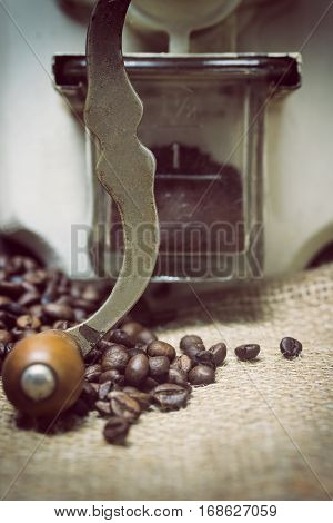Closeup view of the vintage photo of the manual coffee grinder standing on the sackcloth. Around it are scattered coffee beans. Vertically.