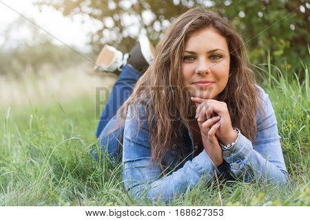 Cool attractive teenage girl is lying face to the camera in grass outdoors