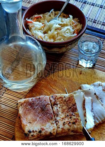 Homemade lard with condiments. Carafe and a glass of vodka, sauerkraut. Natural food, appetizer. Closeup. Traditional Dishes of Russian Cuisine