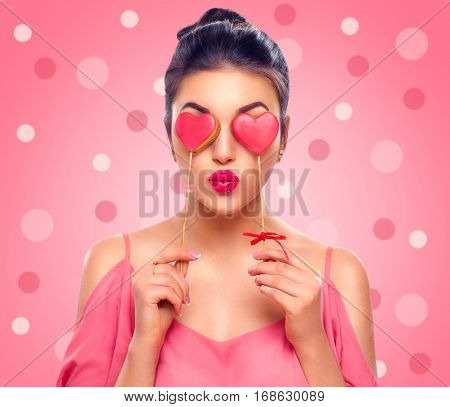 Beauty joyful Young fashion model Girl with Valentine Heart shaped cookies in her hands. Love Concept. Beautiful smiling young woman. Valentines Day gift. On pink polka dots background