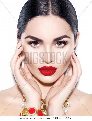 Gorgeous Young Brunette Woman face portrait. Beauty Model Girl with bright eyebrows, perfect make-up, red lips, touching her face. Sexy lady makeup for party. Isolated on white background