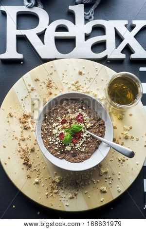 Chocolatiers breakfast with oatmeal, puffed rice, cereals and dried strawberries and green tea prepared in a white bowl. Big inscription Relax above