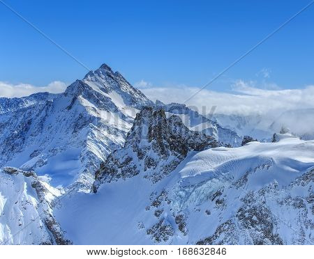 Alps, view from the top of Mt. Titlis in Switzerland in winter. Titlis is a mountain of the Uri Alps, located on the border between the Swiss cantons of Obwalden and Bern.