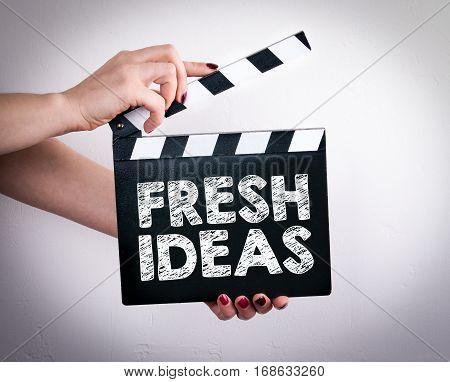 Fresh Ideas concept. Female hands holding movie clapper.