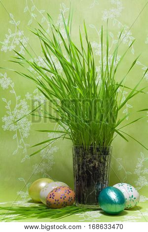 Painted Colorful Easter Eggs and glass with green Grass