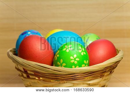 Colored easter eggs with flower of bergenia laying in wood basket