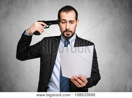 Businessman poining a gun to his head while reading bad news