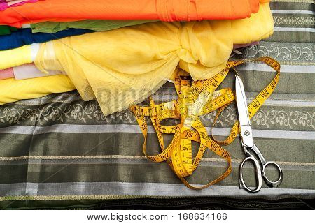 Sewing textile or cloth. Work table of a tailor. Textile tools. Scissors measuring tapes. Top view. Copy space.