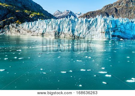 Glacier Bay Alaska cruise vacation travel. Global warming and climate change concept with melting ice. Cruising boat towards landscape of Johns Hopkins Glacier and Mount Fairweather Range mountains.