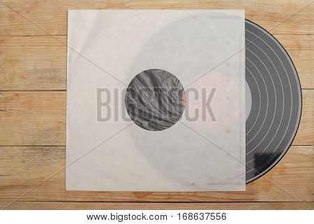 Retro styled image of a collection of old vinyl record lp's with sleeves on a wooden background.