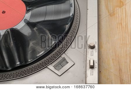 Detail shot of a record player.Vinyl record with copy space in front of a collection of albums dummy titles isolated on white background. vintage process.