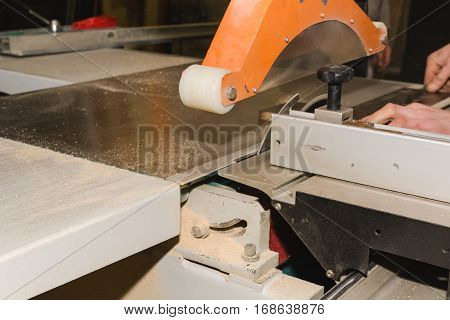 Men at work sawing wood. Circular saw. A machine which saws wood particle Board and fiberboard. Industrial production of furniture.