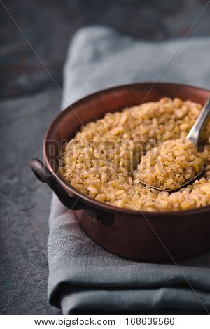 Grain bulgur in a copper bowl and metal spoon partial blur vertical